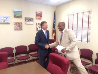 Alan Briggs, Executive Director of the NC Association of Food Banks, shaking hands with McKinley Wooten, Chairman of the State Employee's Credit Union (SECU) Foundation's Board of Directors