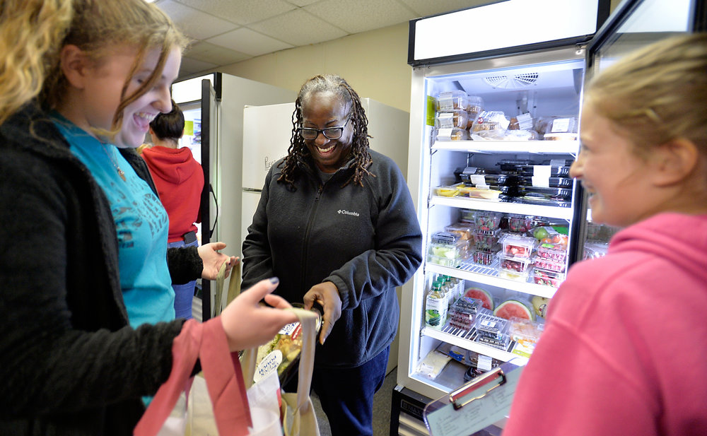 Rosa Lee Robinson, 54, finds a fresh salad she likes from the West Johnston Food Pantry as student volunteers Abigail Jones and Kristen Suggs (right) assist on Wednesday, December 14, 2016 in Benson, N.C. The pantry is a student-led non-profit, which is run out of the West Johnston High School and serves families in need of food in the Cleveland township area. (Photo by Sara D. Davis)