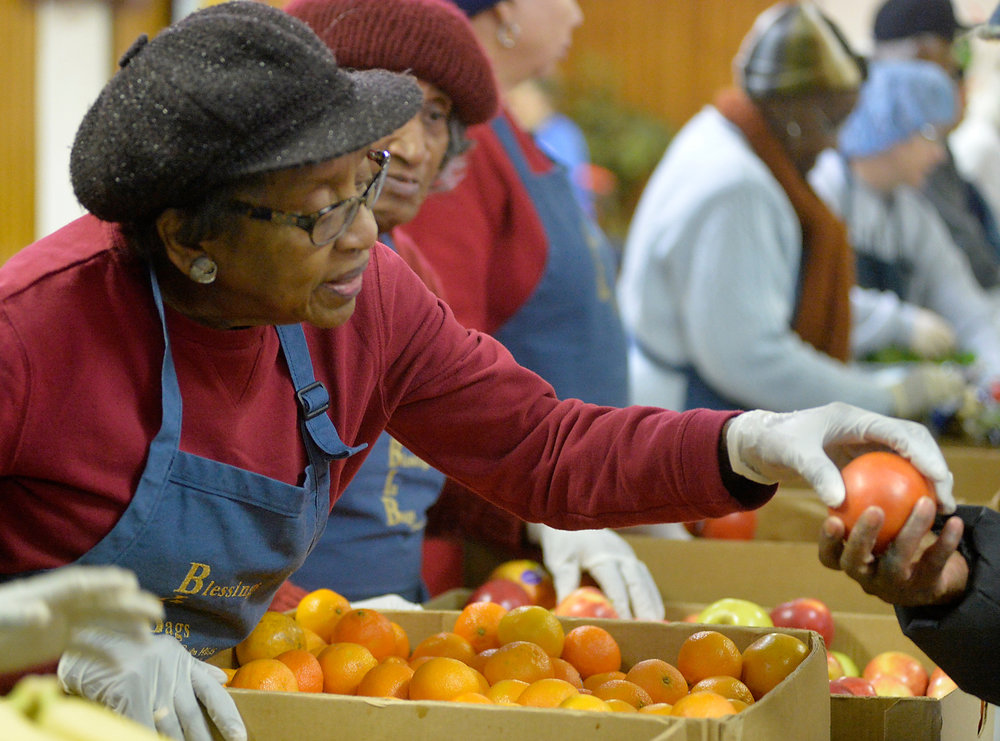 Volunteer Doris Alston hands someone a fresh tomato at the Martin Street Mobile Market in Raleigh, N.C. on Saturday, December 10, 2016. The Inter-Faith Food Shuttle provides some of the fresh food for market. (Photo by Sara. D. Davis)