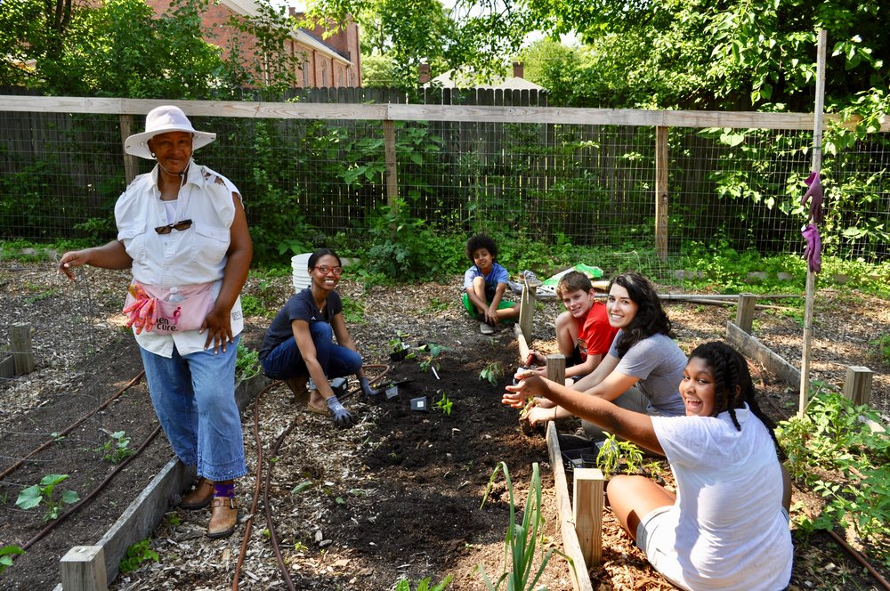 Deborah, a local community member, and Katie Murray with some of the Hunger Heroes students working at the Camden Street Learning Garden.