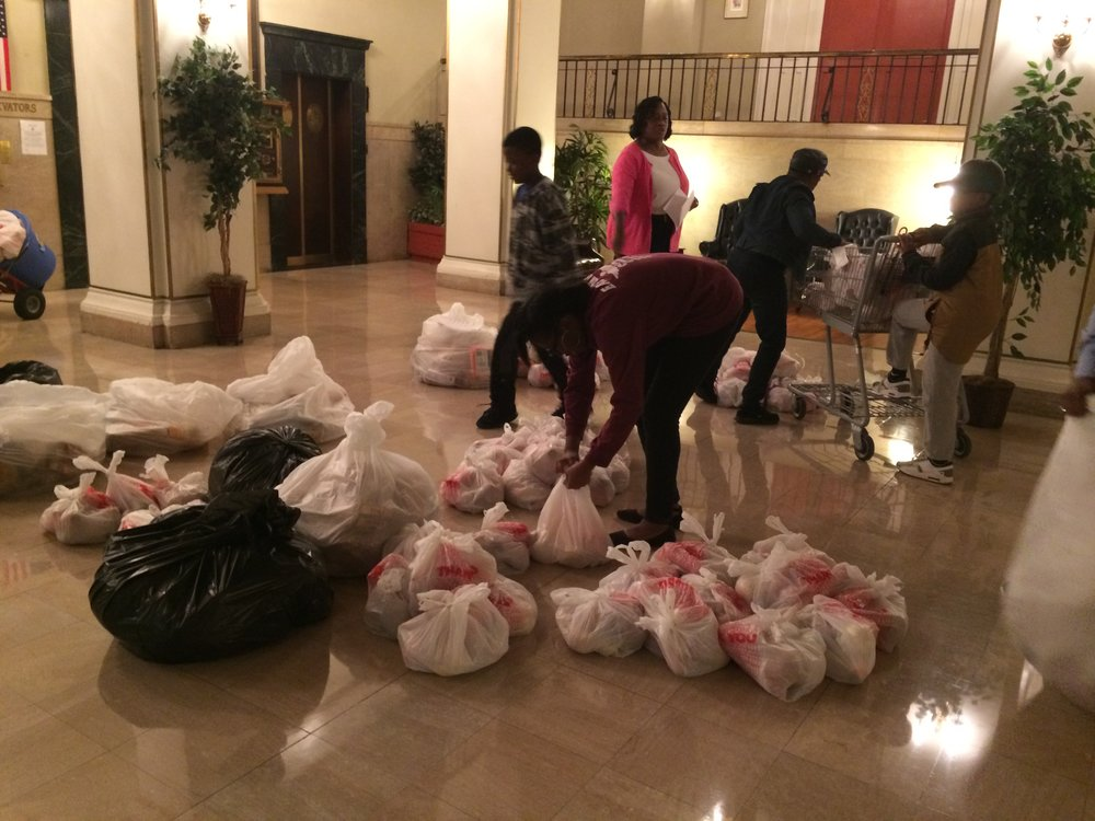 (Above:) Volunteers arrive at Sir Walter Raleigh Apartments and begin sorting through packed produce bags as well as loaves of bread to deliver to individual rooms.