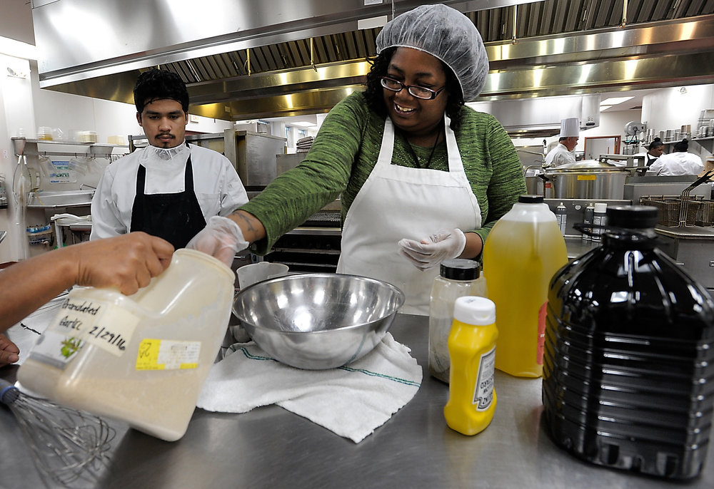 Making a dressing in the Food Shuttle kitchen
