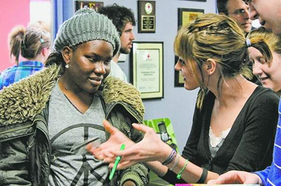 Invisible Children representative Achiro Fionah, left, listens to Kensington Woods High School senior Kyra Gregor for the school's project on the Invisible Children program, which raises awareness of child soldiers exploited for the ongoing conflict in Northern Uganda. / SUBMITTED PHOTO