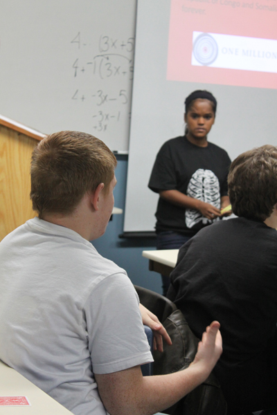 Sophomore CJ Blagborne discusses the effects of genocide with the class and Senior and presenter Deepika Schild.
