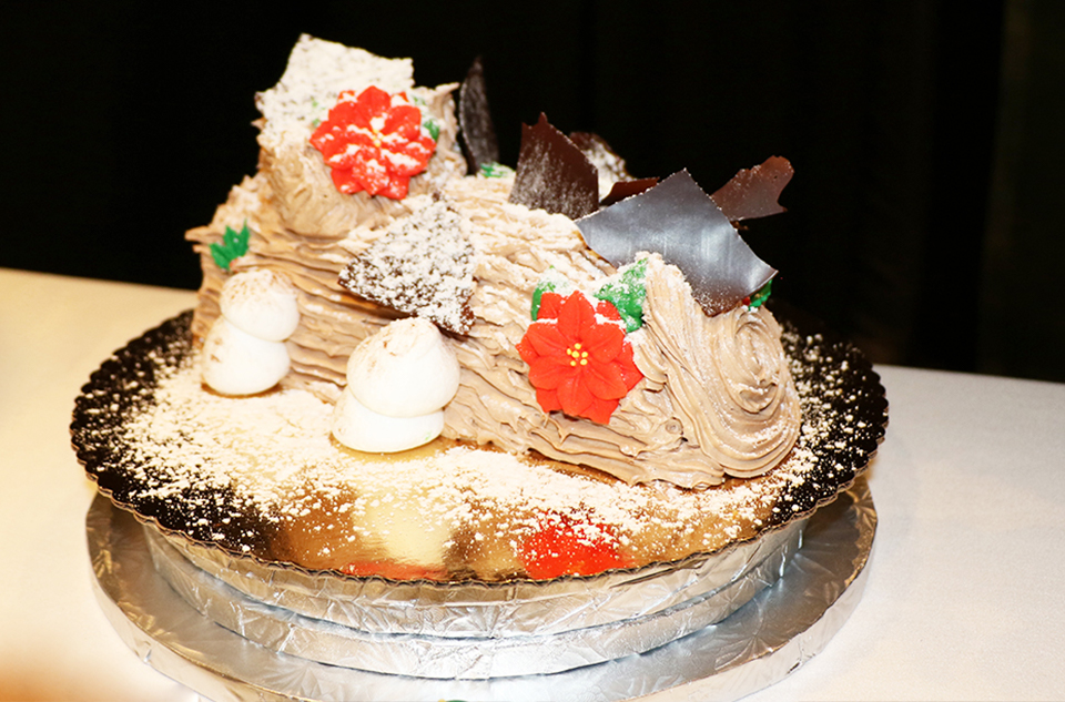 Buche de Noel - Chocolate cake rolled around whipped cream, iced in chocolate butter cream with meringue mushrooms.