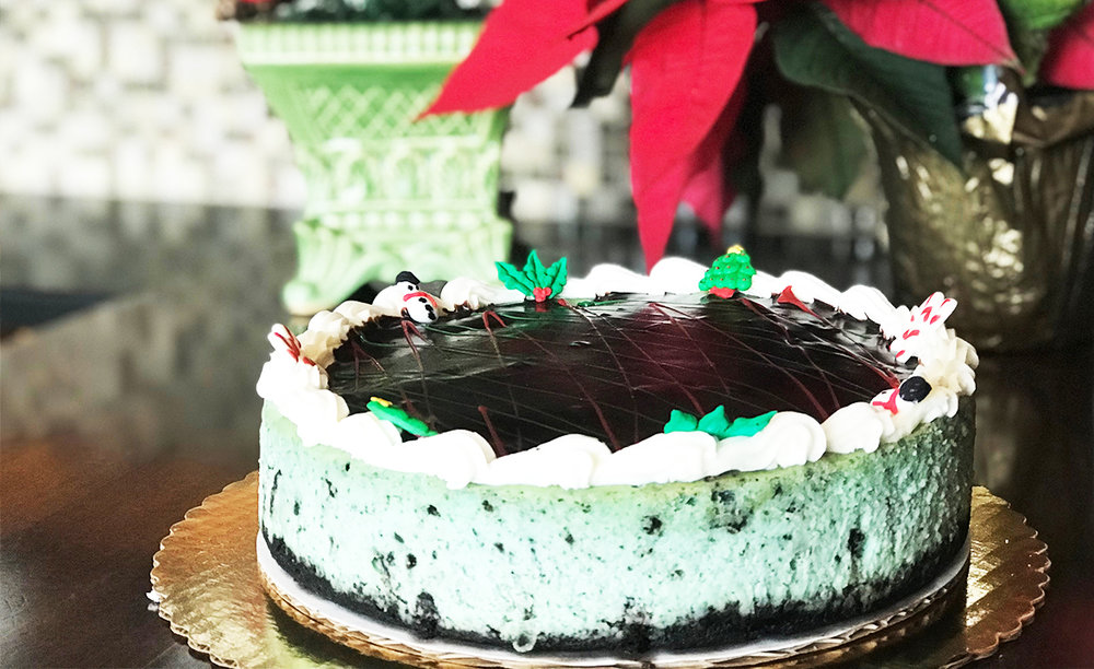 Oreo MintCheesecake - Topped with chocolate ganache and decorated festively.