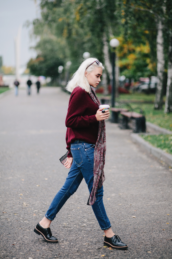 Girl wearing red sweater and holding coffee