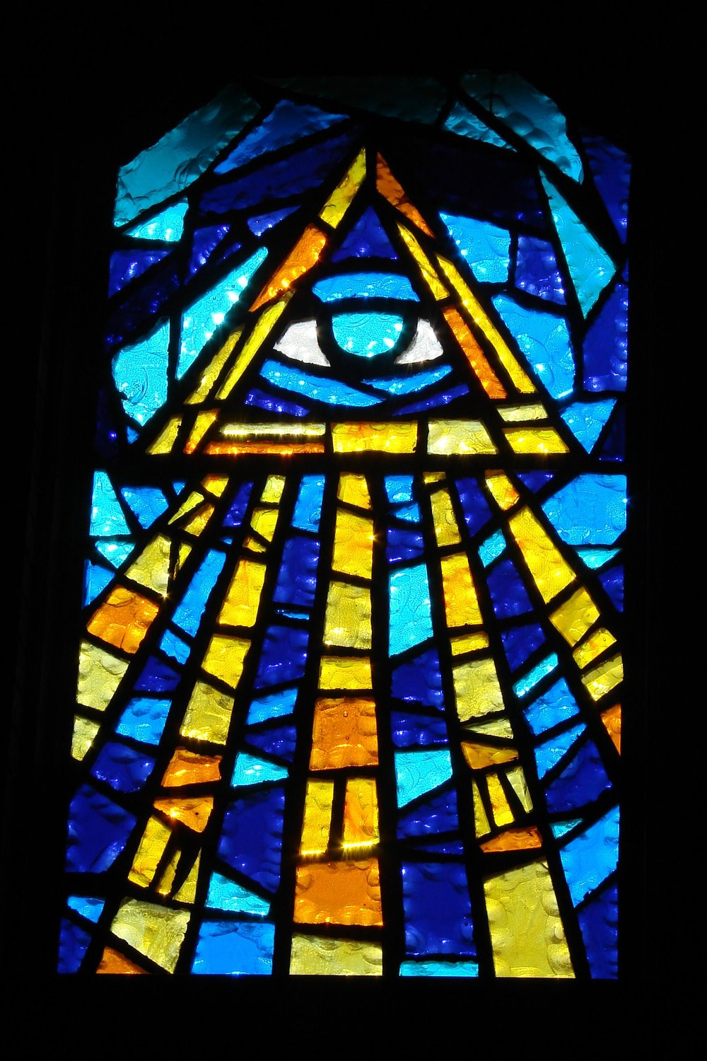 "EYE OF GOD WINDOW - The upper left window is called the EYE OF GOD window.  Within the triangle, symbolizing the Trinity, is an eye, and below that ""rays of the Holy Spirit.""  The eye is to remind us that God watches over us not only when we are in church but eternally saying, ""I will be with you always, even unto the end of time."""