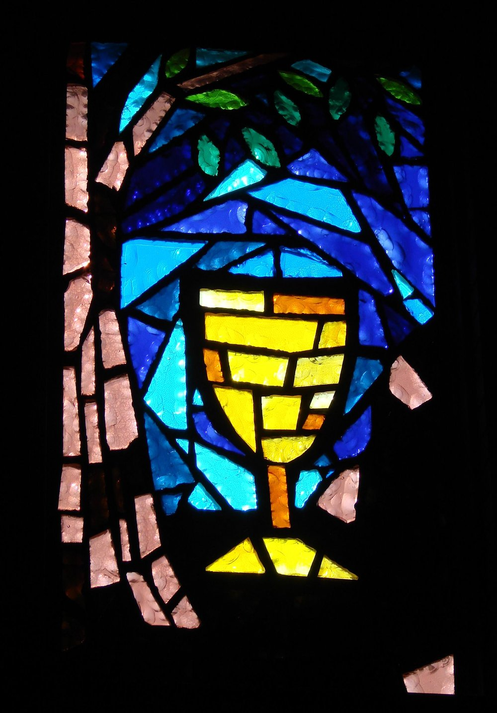"DECISION WINDOW - The symbols in this window are the olive tree and the chalice.  This symbolizes that time just prior to His crucifixion when Jesus went into the Garden of Gethsemane.  There he agonized about whether he would proceed on the course His life in God was taking him.  The Bible says he fervently prayed, ""Father, if it is possible, let this cup pass from me, but not my will but thine be done"".  This moment in Christ's life has been referred to as the greatest decision He had to make."