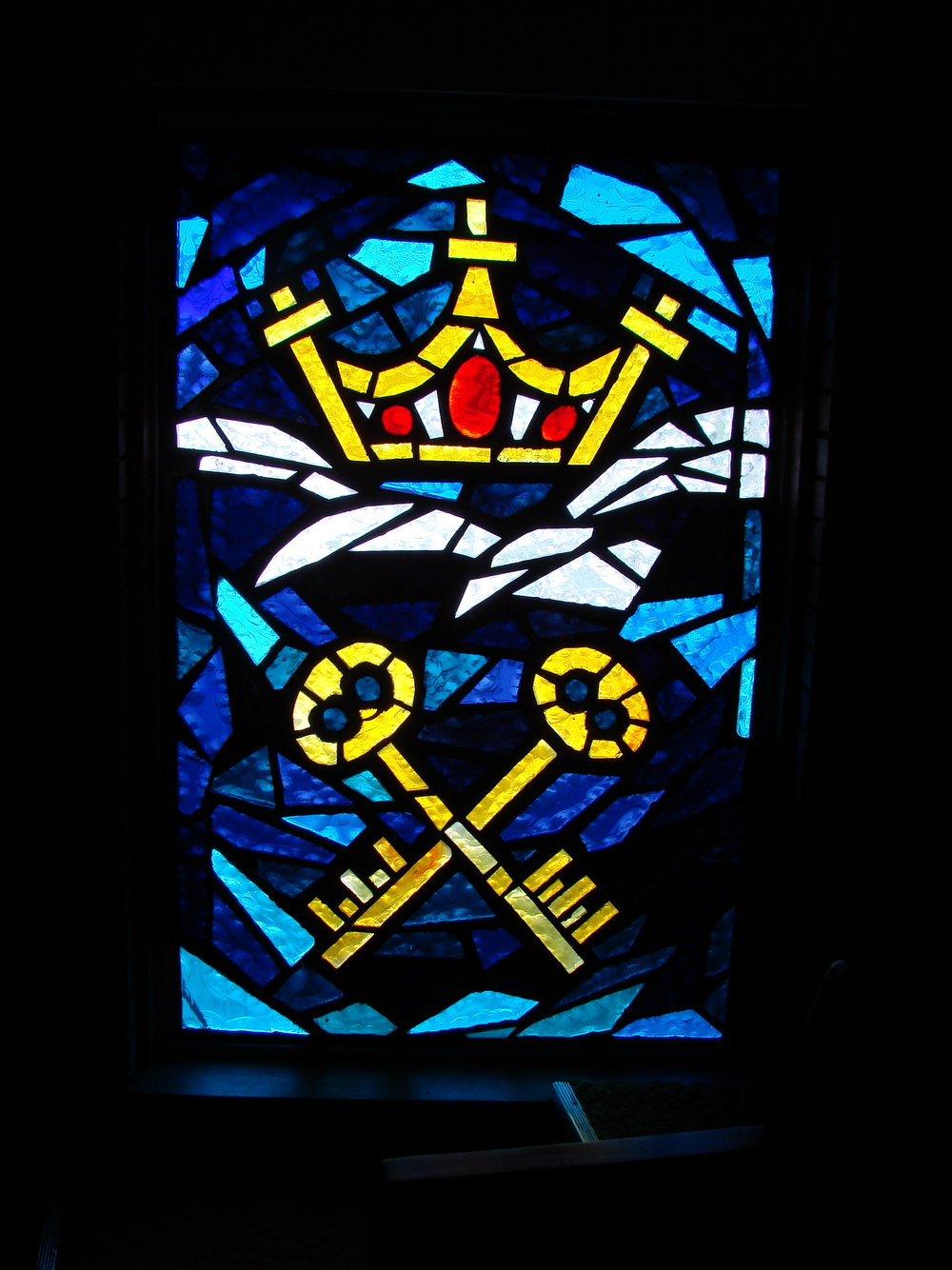 "KEY AND CROWN WINDOW - In the lower portion are two keys that are crossed.  These represent the statement made to Peter: ""I will give you the keys to the kingdom of heaven, and whatever you bind on earth shall be bound in heaven""  God gives us the keys of life, to experience the best or the worst, the good or the bad, justice or injustice.  Jesus Christ set the example.   Above these keys are the symbols of the cross and crown.  They assure us that if we are faithful to Christ's teachings we will inherit the crown of life now and in eternity."