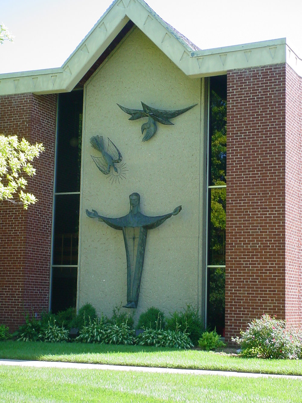 "OUTDOORS TRILOGY - On the outside wall of the east end of the Sanctuary building is an art sculpture arrangement known as the Trilogy.  Symbolically represented are:  God the Father; God the Son; and God the Holy Spirit. Central to the Trilogy is a figure to represent Jesus Christ with outstretched arms as if inviting anyone who would come to Him.  It might well represent Christ's statement, ""And I, if I be lifted up, will draw all to me.""  Above, and a little to the right of this figure, is an open hand reaching downward which could be interpreted as expressing, ""This is my beloved Son in whom I am well pleased,"" and also as God's open hand extended to us all.  Above and a little to the left of the Christ symbol, is a descending dove to represent the Holy Spirit coming down to us all.  This Trilogy has become an identifying feature of our church."