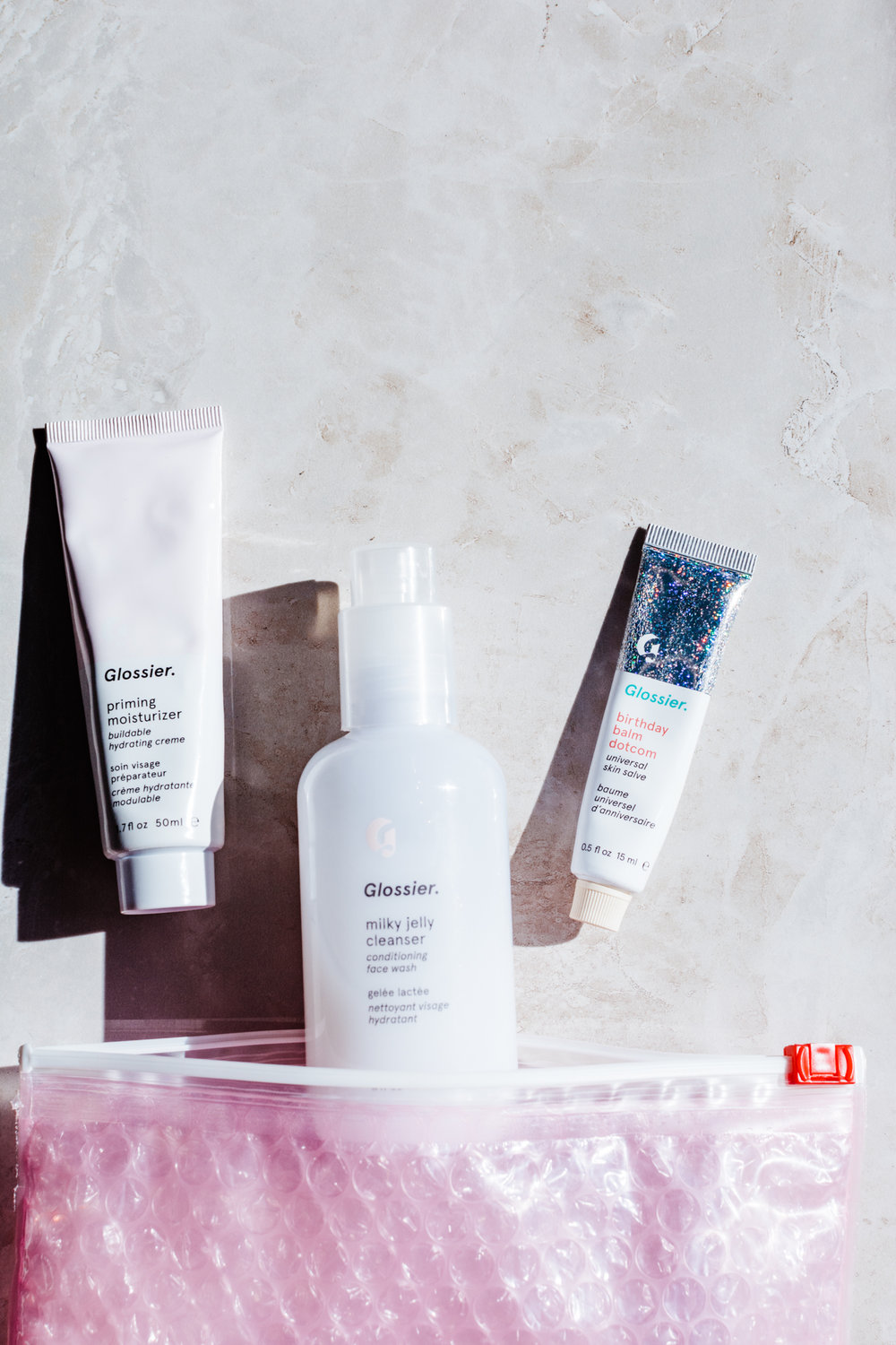 glossier flatlay priming moisturizer milky jelly cleanser balm dot com cake  - styleapotheca