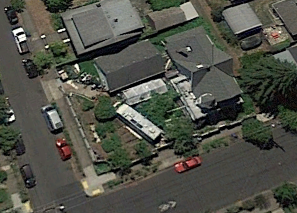 July 2015.  This is the most recent image on Google Earth. On the property, you see the house, garage, an RV, and temporary structure with a white vinyl covering. You also see a Sprinter van on the street. In the upper right corner of the property, you can see how the black berries have grown over the junk. You can just barely see small boat poking out from under the berry bush.