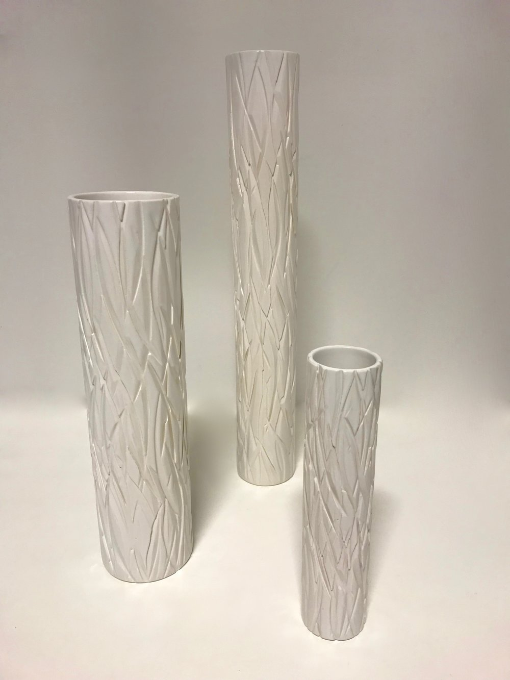 Cut Vases are high fired porcelain ceramic cylinders with a deeply carved surface texture that is applied by using a large industrial saw.  Materials: Ceramic  Dimensions: Tall Vase – 500mm tall x 80mm diameter (approx)  $269  Large Vase – 400mm tall x 100mm diameter (approx) $269  Small Vase – 250mm tall x 60mm diameter (approx)   $149
