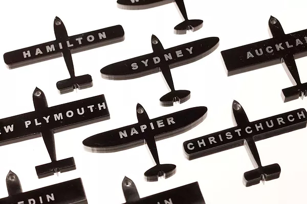 Destination Planes with names of cities, towns or countries.  Materials: Black laser cut resin with top hole for hanging. Can also be converted into a necklace or brooch.  Dimensions: 60 x 45 x 5mm, - not all shapes available for each word (Plane Oval, Plane Square, Plane Spitfire) $36ea Custom made planes special order designs/words $65ea