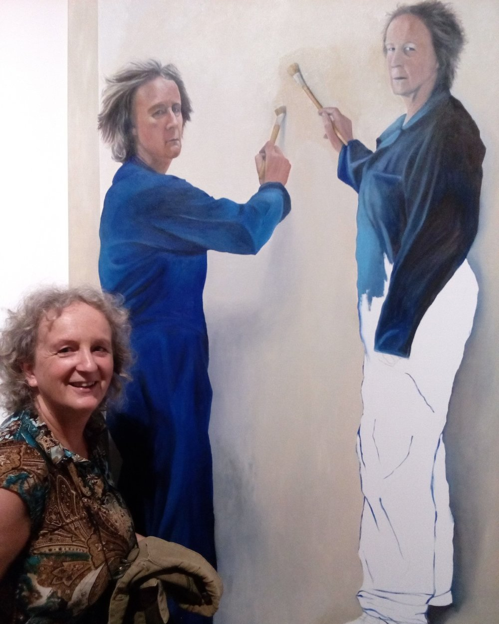 Susan Mabin standing next to her self portrait which was selected for the 2018 Adam Portrait Award