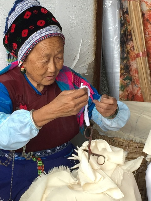Lady stitching designs on fabric in preparation for the indigo dye bath. Yunnan Province, China.