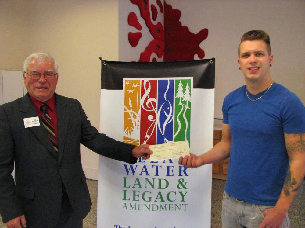 Lake Region Arts Council Board member, Jim Arvidson, presents an Artist Legacy Grant to artist Sam Norman.