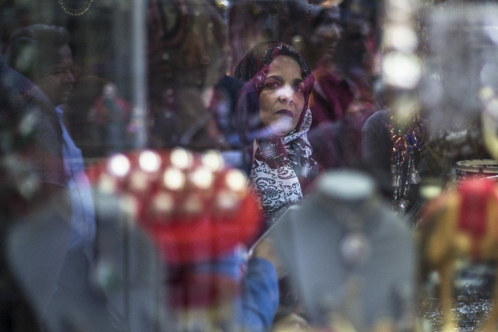 A woman looks out from a store window in downtown Amman, Jordan on June 4, 2015.