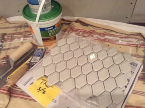 Supplies for installing the tile surrounding the fireplace insert; hexagonal mosaic tile, a small tub of premium mortar, and trowels in various sizes.