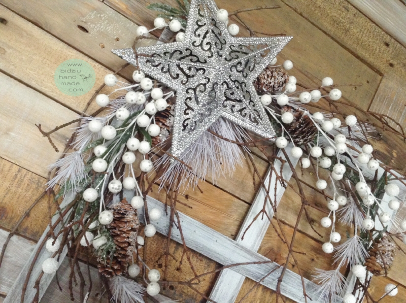 Rustic window christmas frame featuring a sparkling silver star, winter greens, natural branches, pine cones, and white berries.