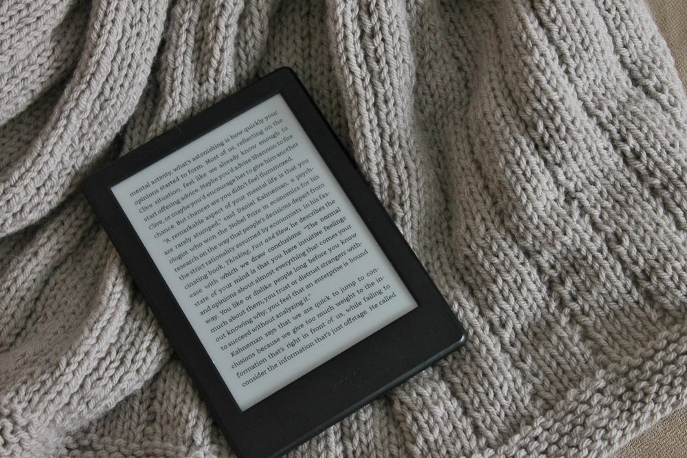 Kindle reader on knitted blanket