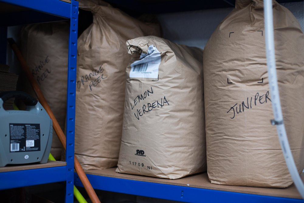 The shelf holding sacks of dry ingredients used to flavour the different gins.