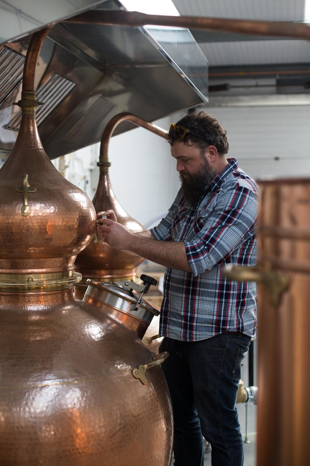 Shaun checks the temperature gauge on one of the copper stills in which the gin is distilled.