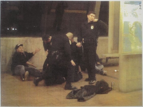 Carlos Reyes, far left, attempts to explain to BART police that Oscar Grant is trapped on top of his leg, as Johannes Mehserle, rear, glances at his gun, mere seconds before shooting Grant in the back. Photo via L.A. County Superior Court.