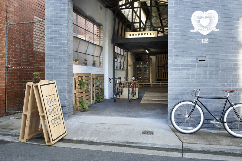 Вело-магазин - Две дървени палети са хванати една за друга чрез панти и въже и съвсем минималистично боядисани, колкото за да се създаде един съвсем семпъл дървен знак, който да казва на хората че вело-магазинът е отворен.