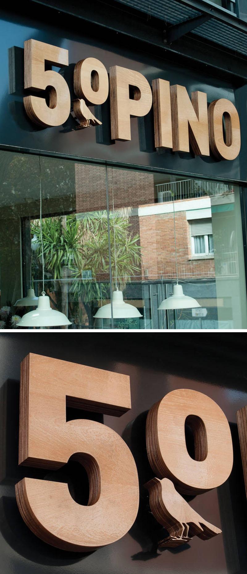 Ресторант - Няколко пласта дърво са нарязани и слепени един върху друг, за да създадат един солиден дървен 3D знак, обозначаващ името на ресторанта.