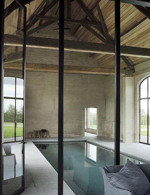 Реновирана със стил - Тази къща с басейн в белгийска провинция е била стар хамбар, от който са запазени автентичните дървени греди и рамка; басейнът е вкопан и облечен в стъклени мозаечни плочи, а около него е покрито с белгийски син камък.