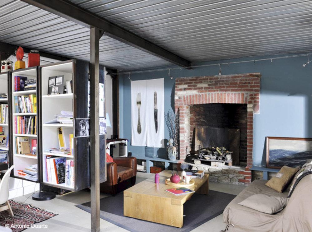 Съвременна... - Пример засъвременен редизайн на всекидневната към това таванско помещение, в което дизайнерите са съумели да запазят и подчертаяткрасивата тухлена камина. Чудесна е комбинация отчервени тухли и бледи сини стени.