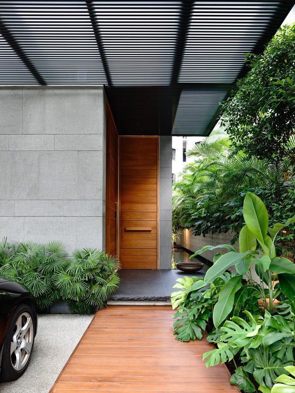 Естествената - Понякога една дървена врата би могла дапридадеестествен характер на бетонните фасадни повърхности. В този пример, една подходяща настилка допълнително разграничава входната врата от павирания паркинги теракотните плочки.