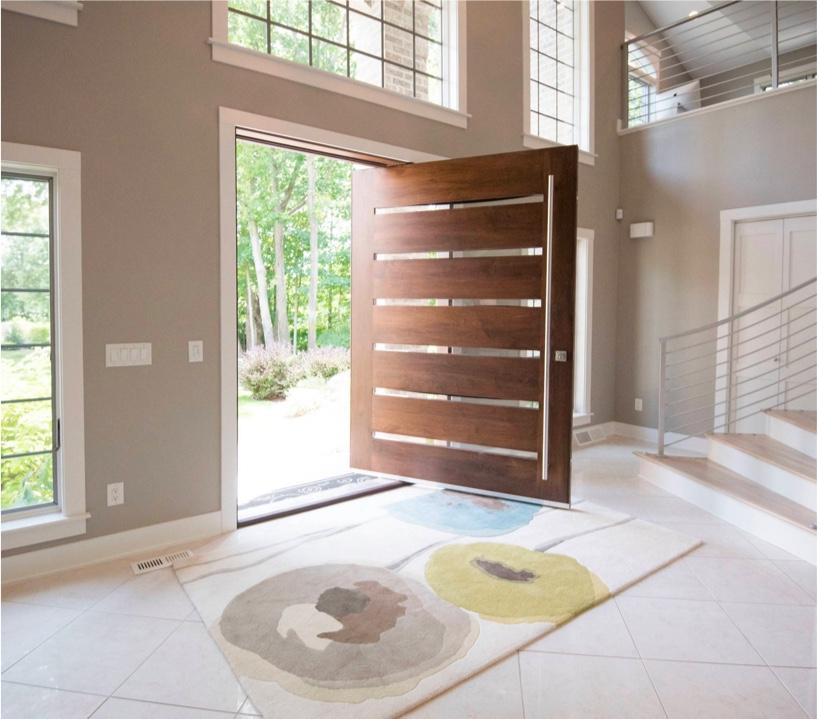 Въртящата - Дървените дъски и редуващистъклени ивици позволяват визуална непрекъснатост, а слънчевата светлинасе филтрира през врата, която иначе изглежда тежка. Дългата дръжка на вратата е още един интересен акцент.