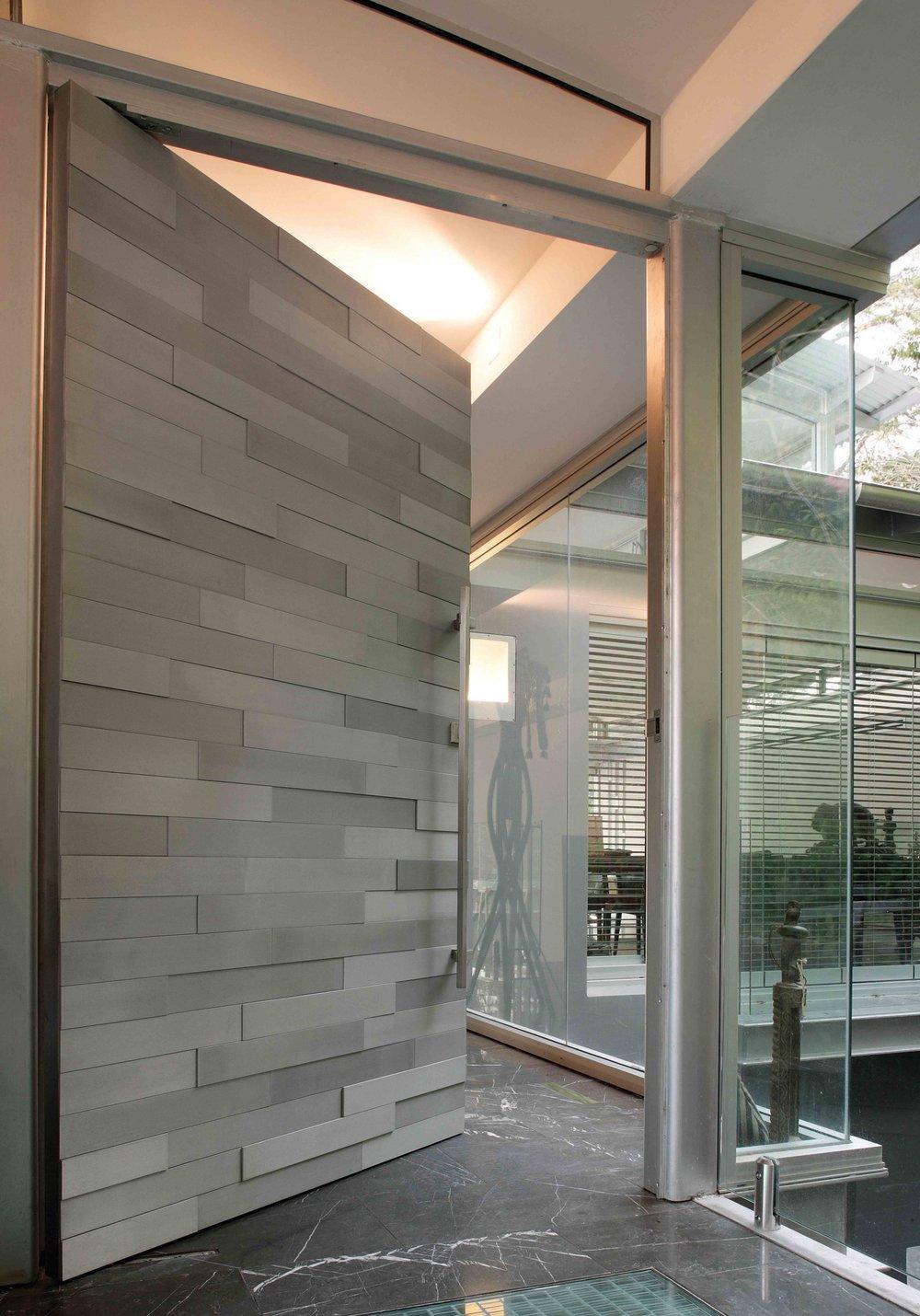 Необичайната - Пример за това как необичайните материали могат да превърнат обикновенавходна врата в истинска отправна точка на едно жилище. В този пример имаме смел подход към текстурата, а каменните панели се различават по нюанс и височина.