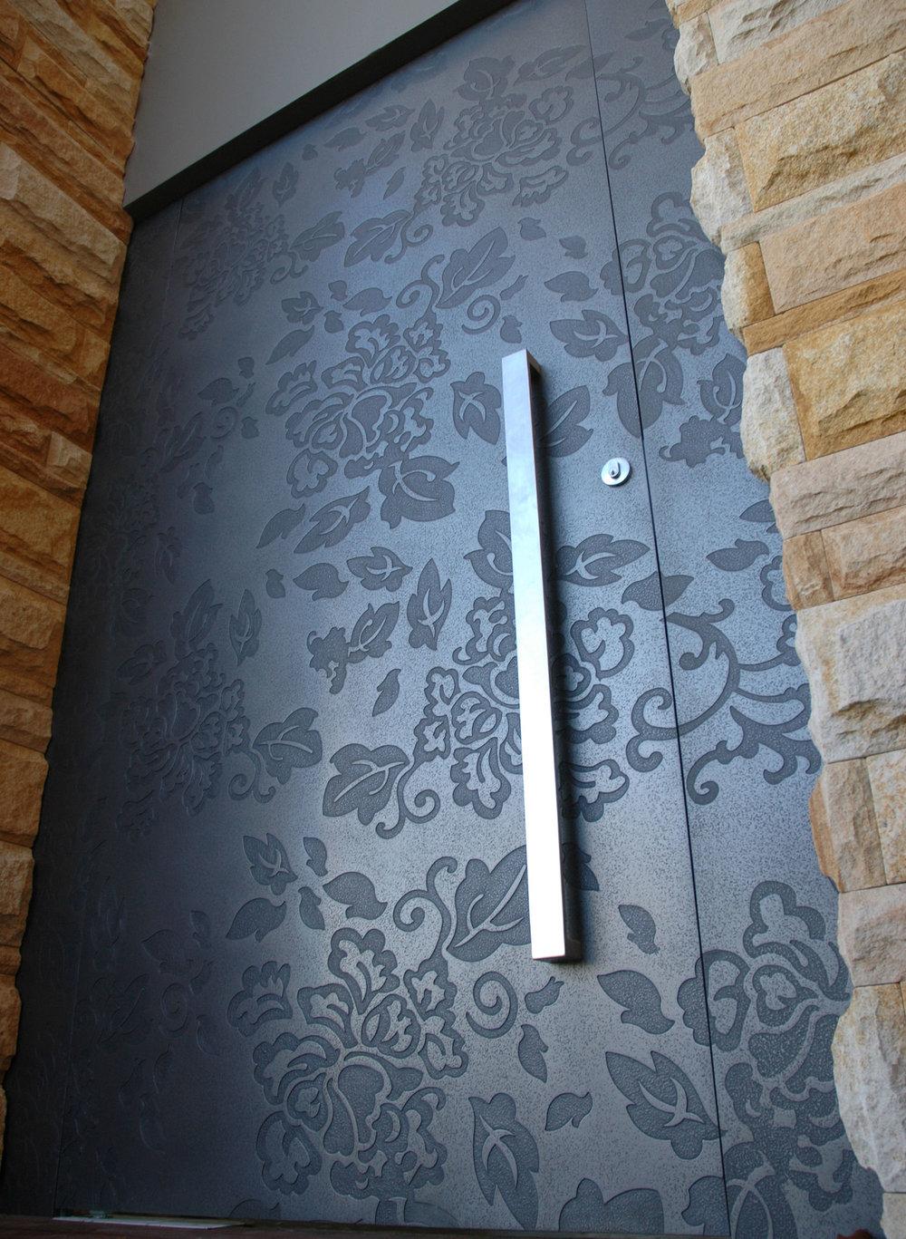 Гравираната - Лазерно-гравиранитеврати дават на собствениците на къщи безкрайни възможности за самоизява. Този флорален отпечатък продължава по протежение на рамкатаот двете страни, за да се продължиефектът й върху екстериора на дома.