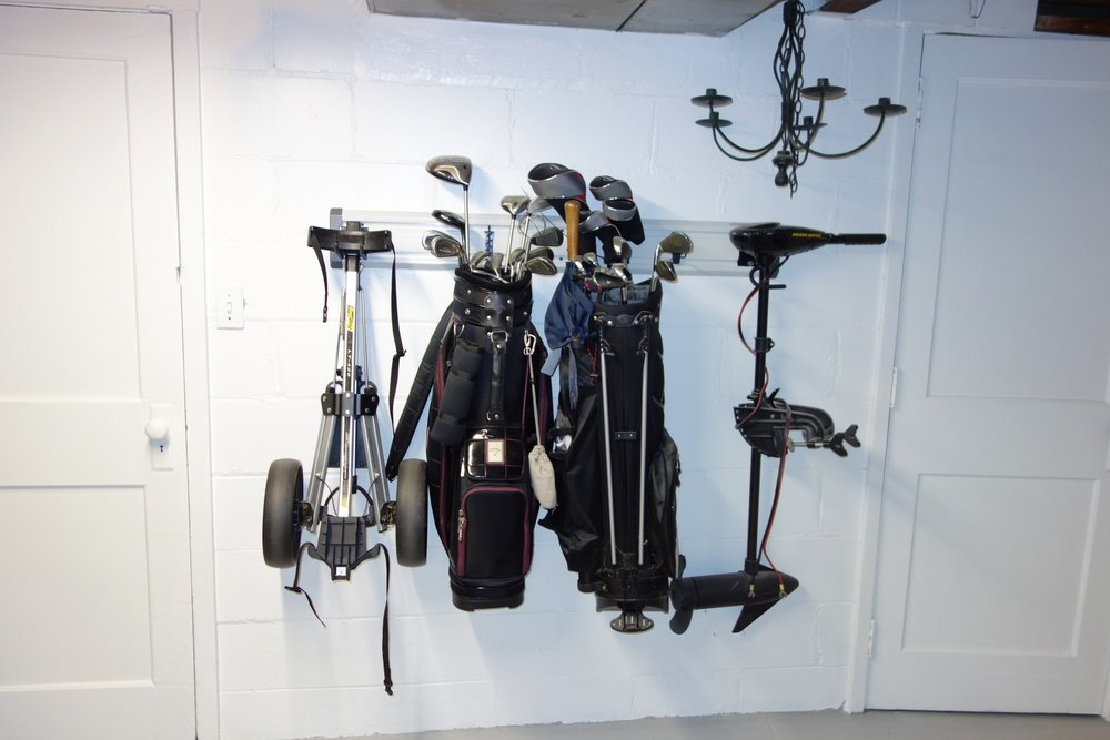 """Get those golf bags off the ground and away from basement critters. Geartrak holds a lot of weight easily when properly mounted. The two golf bags and electric boat motor above all weigh """"a lot""""."""