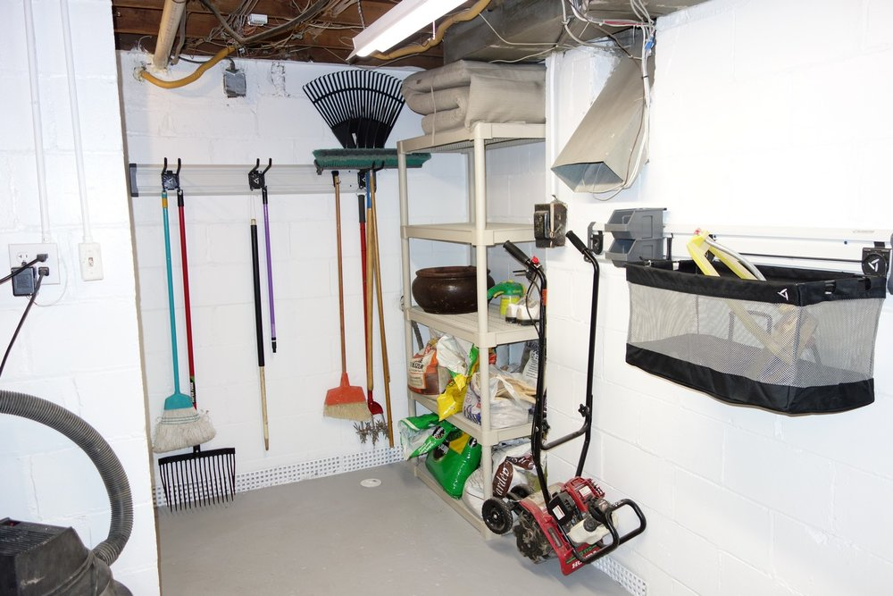 """My """"Gardening Corner"""". An S-Hook holds my heavy rototiller off the ground in my power tool room. That's nice because I am frequently sweeping up sawdust in here. Tool Hooks easily hold my brooms and yard tools, with lots of room to spare. I haven't decided yet how to use the 24-inch mesh basket that came in the Accessory Kit - will probably put sprinklers and various hose nozzles in it."""