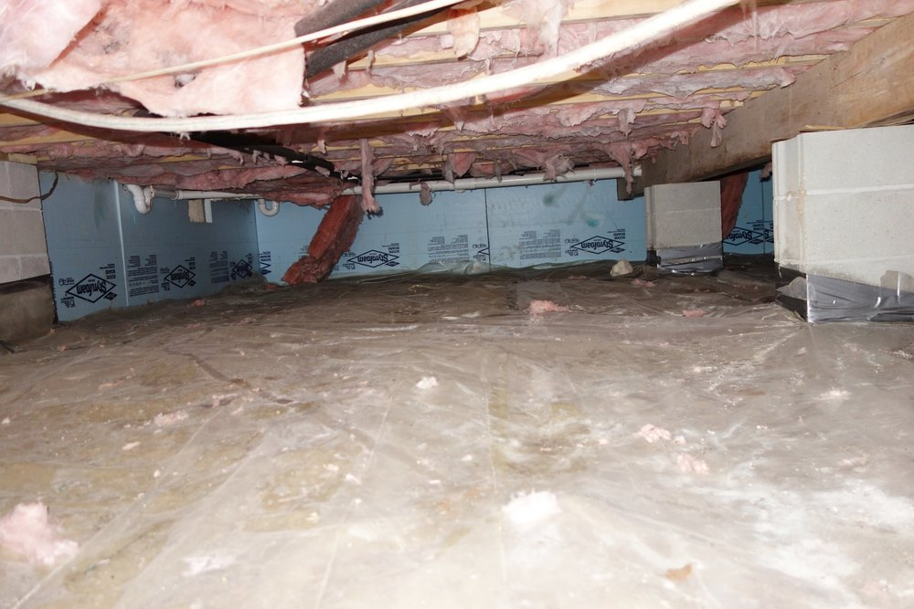Here's the newer part of my crawl space before the project. Floor insulation falling down, but the walls were insulated with foam board. There were 2 layers of plastic on the ground, and even though there was some moisture underneath them, sealing the plastic well would keep that moisture out of the crawl space.