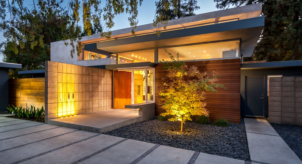The warm cedar, polished concrete block and wide mahogany pivot door invite you in.