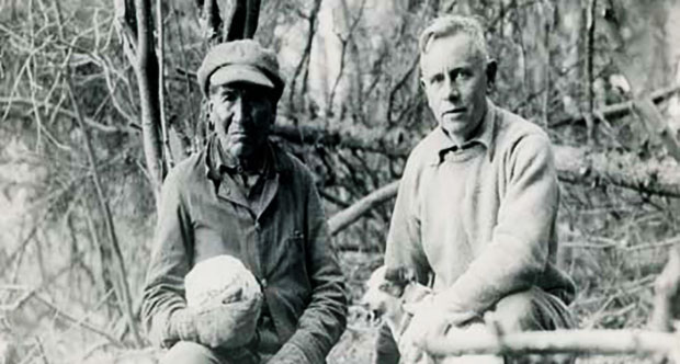American explorer, author and conservationist Ernest Oberholtzer (right) with dog Skippy and Ojibwe trapper and guide Billy Maggie (left) holding cabbage.