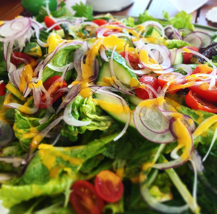House salad topped with a carrot ginger orange vinaigrette