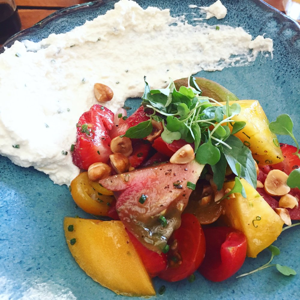 Fresh local tomatoes and strawberries create this beautiful Hierloom Tomato and Strawberry salad with house whipped ricotta and fried hazelnuts.
