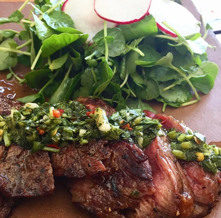 Medium rare flap steak topped with a fresh chimichurri sauce