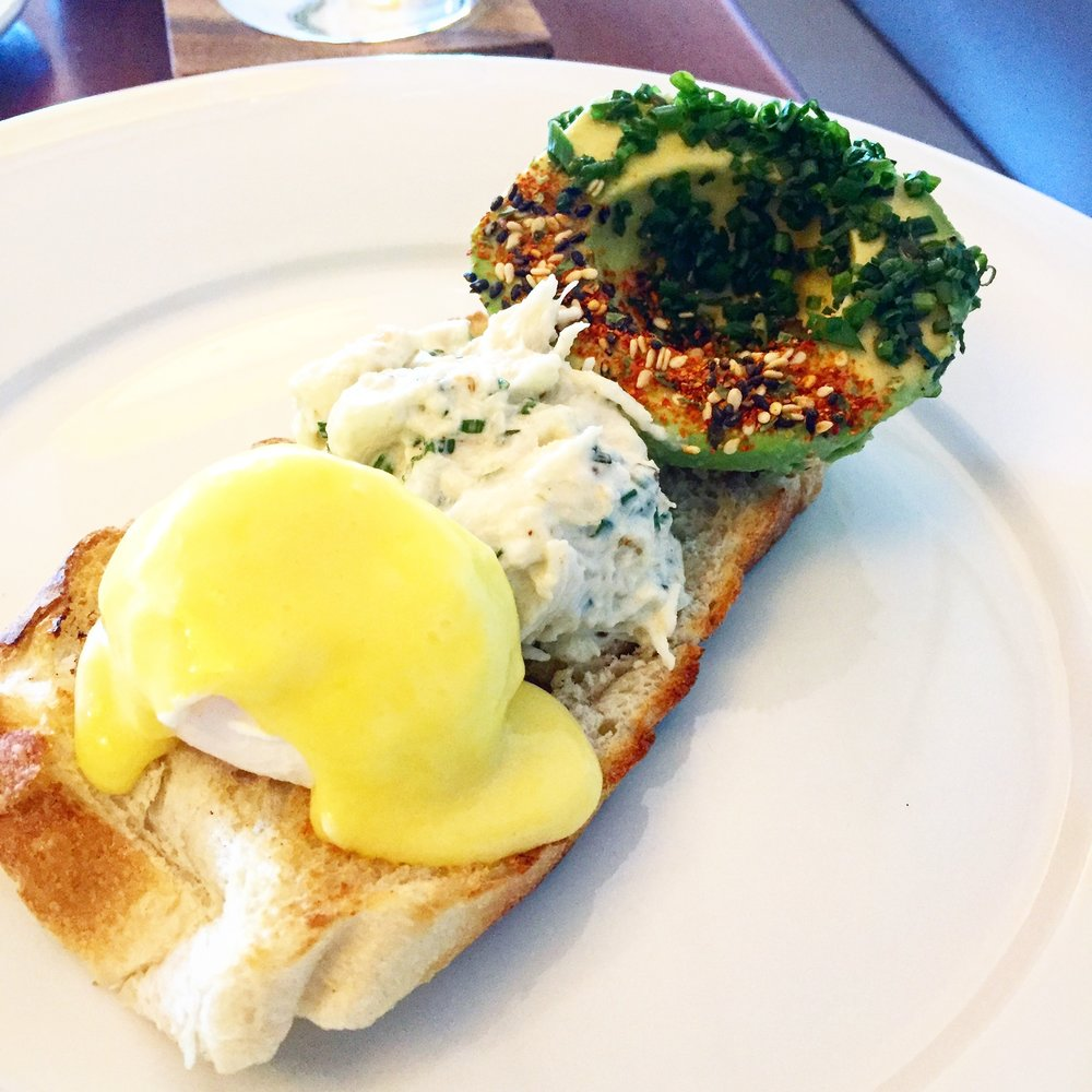 Poached egg with hollandaise, light crab salad and togarashi sprinkled avocado all on a crusty bread.