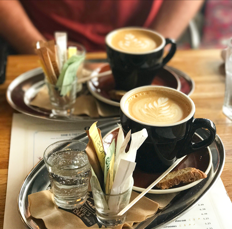 Lattes served with biscotti and sparkling water
