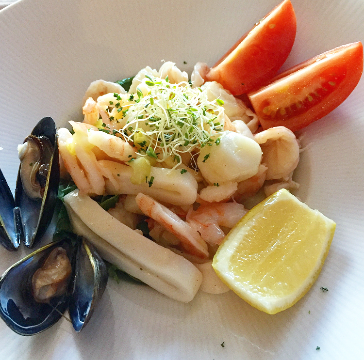 The refreshing and light Seafood Salad: shrimp, scallops, mussels, lobster and calamari marinated in olive oil, lemon and garlic and served on a bed of arugula