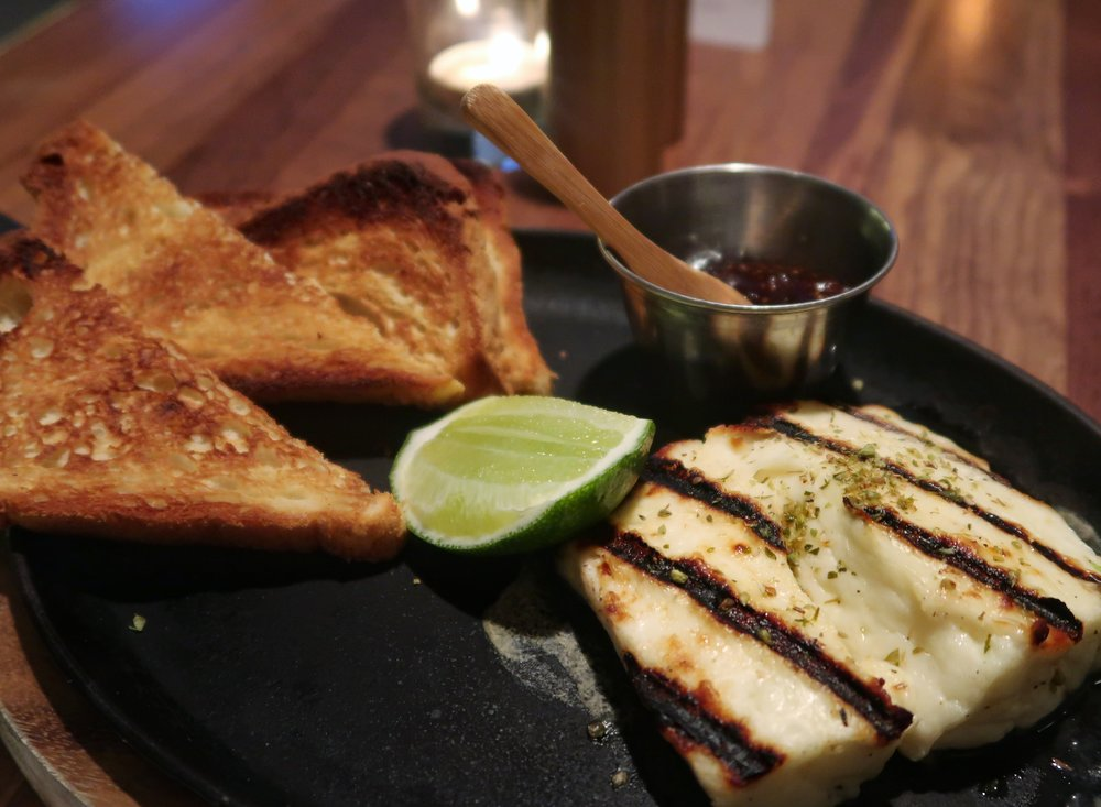The rich and smoky Halloumi Cheese Flambé served with grilled sourdough (or GF toast), lime and jam. They'll douse it in vodka before lighting it up for you tableside.