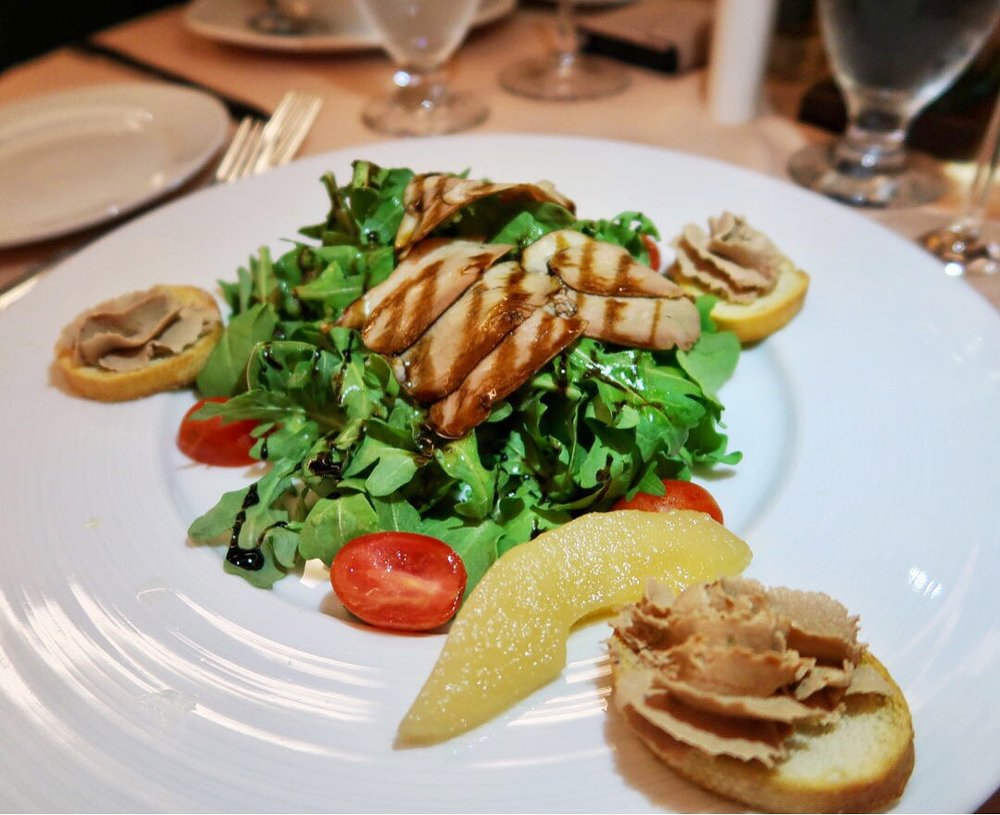 """Smoked Duck Salad: Thinly sliced in-house smoked duck on a bed of arugula, cherry tomatoes, craisins, Calvados pears and a balsamic reduction. Served with chicken liver """"croutons"""" on the side."""